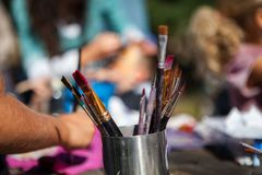 Metal container full of paintbrushes while kids are sitting outside stock photos