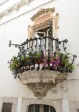 Small window balcony in the village of Locorotondo, southern Italy. Pictured is a baroque style window balcony with plants and flowers in Locorotondo Stock Photo