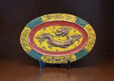 Antique oriental plate, Hue, Vietnam. Pictured is a beautiful antique oriental plate on display in Hue, Vietnam. In the center is an embossed dragon with a small stock image