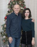 Beautiful young Amerasian woman posed in front of a Christmas Tree with her father. Pictured is a beautiful young Amerasian women posed in front of a Christmas Royalty Free Stock Photos