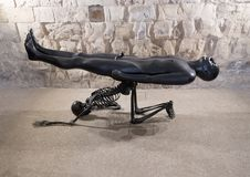 Bronze sculpture naked man supported by kneeling skeleton by Nino Longobardi in a room of the Castel Del Monte. Pictured is a black bronze sculpture by Nino royalty free stock photography