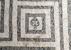 Black and white mosaic tile floor in one of the many bath houses in Parco Archeologico di Ercolano. Pictured is a black and white mosaic tile floor in one of the Royalty Free Stock Photos