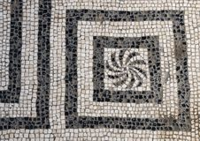 Black and white mosaic tile floor in one of the many bath houses in Parco Archeologico di Ercolano. Pictured is a black and white mosaic tile floor in one of the Stock Photo