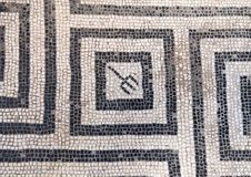Black and white mosaic tile floor in one of the many bath houses in Parco Archeologico di Ercolano. Pictured is a black and white mosaic tile floor in one of the Stock Image