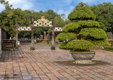 A Bonsai Topiary Tree and small ornate side gate, Imperial City, Citadel, Hue, Vietnam. Pictured is a Bonsai topiary tree in an earthen pot and a small ornate royalty free stock photo