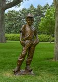 Bronze sculpture of a boy with baseball and glove by Gary Price at the Dallas Arboretum and Botanical Garden. Pictured is a Bronze sculpture of a boy with royalty free stock image