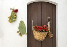 Door decorated with basket of red peppers in the village of Locorotondo, southern Italy. Pictured is brown door decorated by a hanging woven basket of red Royalty Free Stock Image