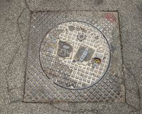 Cast iron drain cover with coat of arms in Alberobello, Italy. Pictured is a cast iron drain cover in Alberobello, Italy.  On the left side of the picture is the Royalty Free Stock Photos