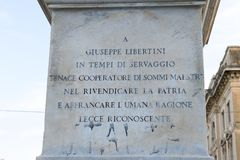 Closeup of writing on a monument with statue of Giuseppe Libertini, Lecce, Italy Royalty Free Stock Photography