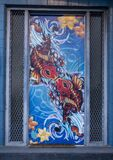 Colorful fish kissing mural on a door in Deep Ellum, Texas.