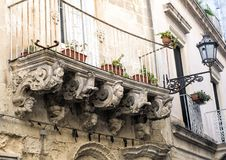 Old crumbling baroque balcony with planters, Lecce Italy. Pictured is a crumbling baroque style balcony housing several red clay planters.  It is enclosed by a Royalty Free Stock Photography
