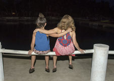 Cousins sitting on a fence rail stock image