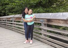 Korean mother affectionately posing with her daughter on a wooden bridge in Washington Park Arboretum, Seattle, Washington royalty free stock photography