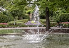 Fogelson Fountain at the Dallas Arboretum and Botanical Garden. Pictured is the Fogelson Fountain at the Dallas Arboretum, with flower beds and hedges in the Stock Photography