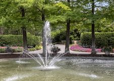 Fogelson Fountain at the Dallas Arboretum and Botanical Garden. Pictured is the Fogelson Fountain at the Dallas Arboretum, with flower beds and hedges in the Stock Photo
