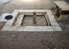 Fountain and mosaic floor in Roman house in Parco Archeologico di Ercolano. Pictured is a fountain, bench and mosaic floor in a Roman house in the Parco Stock Images