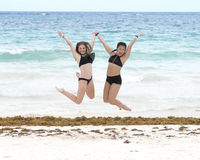 Athletic young girls posing on the beach. Pictured is a fourteen year-old Caucasian girl and her twelve year-old Amerasian cousin dancing on the beach at Playa Stock Images