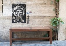 Grafitti showing a spaceman on wall above a bench on a street in Rome. Pictured is grafitti showing a spaceman on wall above a bench on a street in Rome. The stock image