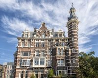 Restored historic building Amsterdam, The Netherlands. Pictured is a historic restored five-story building in Amsterdam, the Netherlands. It has a tower and red stock photo