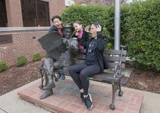 Family posing humorously with bronze of Will Rogers on a bench, Claremore, Oklahoma. Pictured is a Korean mother and her nine and thirteen year old Amerasian Stock Images