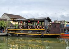 Tour Boat docked on the Thu Bon River in Hoi An, Vietnam. Pictured is a large brown two-story tour boat docked on the Thu Bon River in Hoi An, Vietnam.  Hoi An stock image