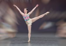 Lovely thirteen yearold Amerasian girl performing a ballet dance. Pictured is a lovely athletic thirteen yearold Amerasian girl performing a ballet dance at a Royalty Free Stock Images