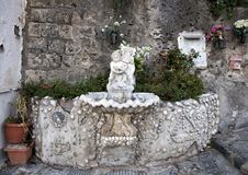 Ornate drinking fountain with small statue of a cherub holding a dolphin, Marina Grande, Sorrento. Pictured is an ornate drinking fountain with small statue Stock Image
