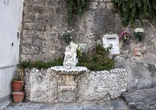 Ornate drinking fountain with small statue of a cherub holding a dolphin, Marina Grande, Sorrento. Pictured is an ornate drinking fountain with small statue Royalty Free Stock Photography