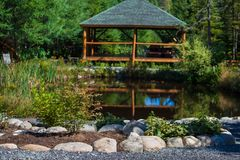 Amazing landscaping project with pond, rocks, plants, flowers and wooden gazebo stock photo