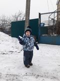 A little boy plays snowballs in the winter stock images