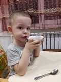 The little boy is sitting at the table and frowning. Pictured in the photo the little boy is sitting at the table and frowning royalty free stock images