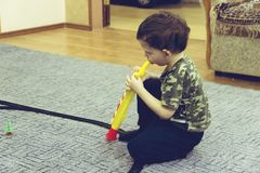 Portrait of cute little boy playing flute in toy royalty free stock photography