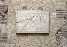 Temple in the College of Augustales in Parco Archeologico di Ercolano. Pictured is a plaque dedicating the College of Augustales, located near the center of Royalty Free Stock Photo