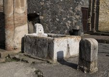 Public water fountain in the remains of Herculaneum Parco Archeologico di Ercolano. Pictured is a public water fountain in the remains of Herculaneum in the Stock Photography