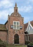 Historic dutch building with Lady Justice Gablestone, 1639, Netherlands. Pictured is a restored 17th century Dutch buildinge in a small town. It has one gable stock image