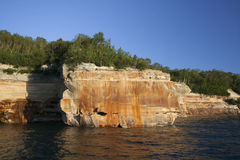Pictured-rocks. Trees and water at Lake Superior upper-peninsula  Michigan. Sandstone mineral colors blue-sky cliff Royalty Free Stock Photography