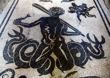 Sea monster on a mosaic tile floor in one of the many bath houses in Parco Archeologico di Ercolano. Pictured is a sea monster on a mosaic tile floor in one of Royalty Free Stock Image