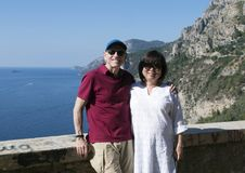 Senior male and Korean wife enjoying vacation Amalfi Coast. Pictured is a senior caucasian male with his Korean wife enjoying a vacation. They are posed along Royalty Free Stock Images