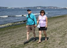 Husband and wife on vacation enjoying a walk on Alki Beach, Seattle, Washington stock photos