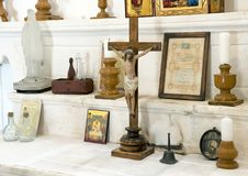 Small statue of Jesus Christ on the cross, surrounded by various objects in a small church at Masseria Il Frantoio, Southern Italy. Pictured is a small statue of stock photo