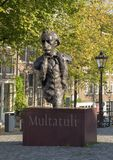 Statue Multatuli on a canal bridge in Amsterdam, The Netherlands. Pictured is a statue of Eduard Douwes Dekker, better known by his pen name Multatuli. It is royalty free stock photos