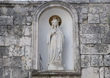 Madonna statue praying, located in a niche in Locorotondo, southern Italy. Pictured is statue of Madonna praying, located in a niche in Locorotondo Royalty Free Stock Image