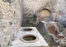 Street food bar with pots to keep food hot in the remains of Herculaneum Parco Archeologico di Ercolano. Pictured is a street food bar with pots to keep food hot Royalty Free Stock Image