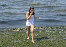 Teenage girl having fun on slime covered Alki Beach in Seattle, Washington. Pictured is a thirteen year old Amerasian girl walking gingerly barefoot on the green royalty free stock photography