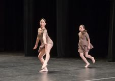 Amerasian sisters perform jazz duet. Pictured are a thirteen year old and nine year old Amerasian sisters performing a jazz duet in a dance competition.  They Stock Photo