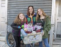 Teenage girls posing for a donation with Diva and Chloe in South Philadelphia. Pictured are three teenage sisters happily posing with Diva and Chloe. Diva is a royalty free stock photos