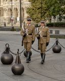 Guards marching in a circle around the flagpole near the Hungarian Parliament Building stock images
