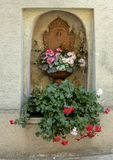 Copper Water spigot and bowl planted with lovely flowers in a niche in a wall, Krems, Austria. Pictured is a wall niche filled with an antique copper water stock photography