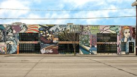 Mural by FAILE on the side of an eatery in Trinity Groves, Dallas, Texas. Pictured is a wild, frenzied display of graphics that seem to tell a story reminiscent Royalty Free Stock Images