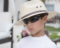 Cool boy on the beach. Pictured is a 10 year-old Amerasian boy wearing a white hat at a jaunty angle, wraparound sunglasses, and a white shirt.  He has his head Royalty Free Stock Photo